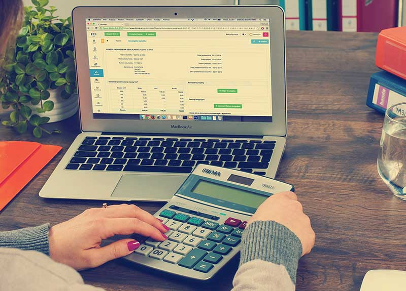 Financial support packages in England – a business owner consulting figures at a laptop