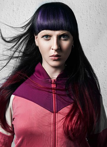 A model with long, dark, straight hair and a deep purple fringe. Taken from the collection 'Clique' by Ciaran Dowd