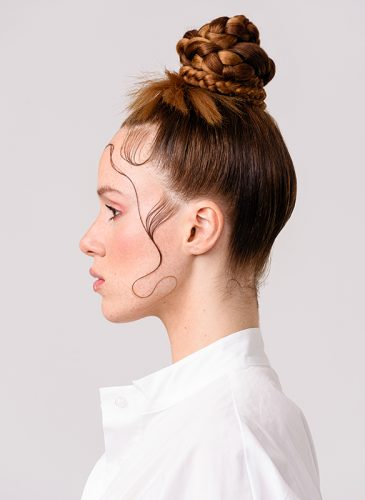 Model with auburn hair in a plaited topknot and gelled baby hairs. Taken from the collection 'Fascination' by Mary Geoghegan