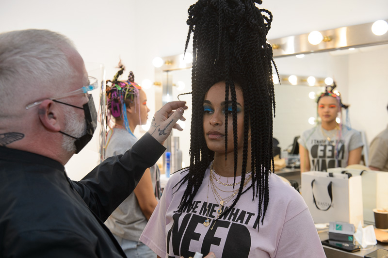 Adam Reed preparing a hair model with long braids in a towering bunbackstage at Creative HEAD Magazine's Salon Smart Live 2021