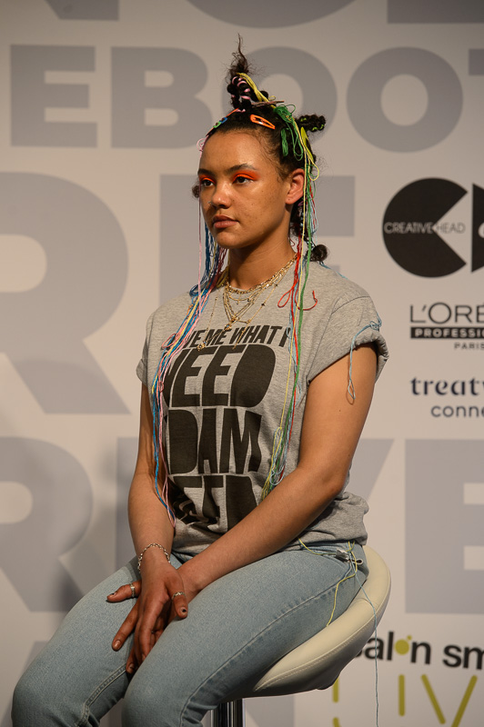 A hair model styled by Adam Reed, with bantu knots and coloured threads draped in her hair, on stage at Creative HEAD Magazine's Salon Smart Live 2021