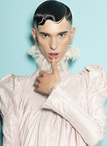 A male model with wet-look finger waves in a high-neck pale pink blouse with ruffle collar, taken from the 'Adore You' collection by the Bad Apple Art Team