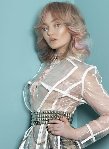 A female model with shoulder-length pale pink hair, styled in a 70s flicked manner with curtain bangs.She is wearing a transparent rain mac and studded belt in a shot taken from the 'Adore You' collection by the Bad Apple Art Team