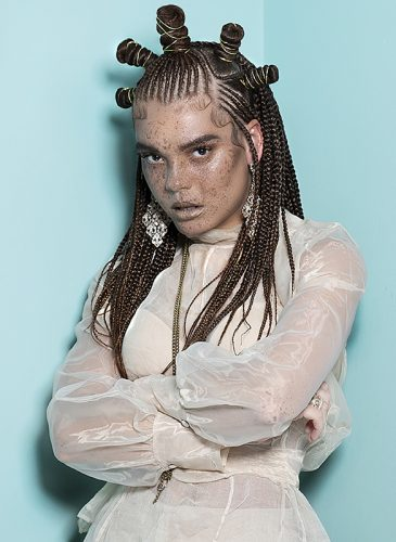 A female model with long brunette hair in fine scalp braids, styled half-up in a series of bantu knots across her crown. She is wearing a a sheer cream blouse, frosted lipstick and silver drop earrings in a diamond shape, in a shot taken from the 'Adore You' collection by the Bad Apple Art Team