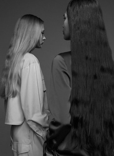 A black and white photograph of two models, standing with their backs to the camera. One has long, straight blonde hair, the other long straight black hair. Taken from the 'Outside The Lines' collection by Helen Kenny