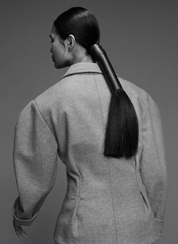 A black and photo of a female model with long, straight, black hair, tied into a low ponytail that is wrapped with a leather ribbon. She is wearing a tweed jacket and facing away from the camera. Taken from the 'Outside the Lines' collection by Helen Kenny