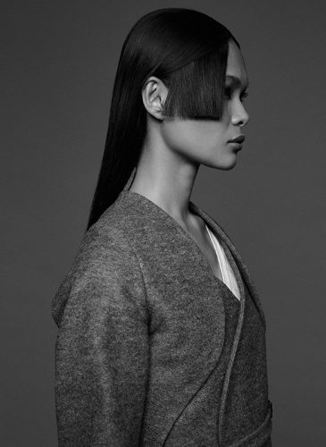 A black and white profile shot of a female model with long, straight, black hair, with a long blunt fringe section cut on her right hand side. Taken from the 'Outside the Lines' collection by Helen Kenny