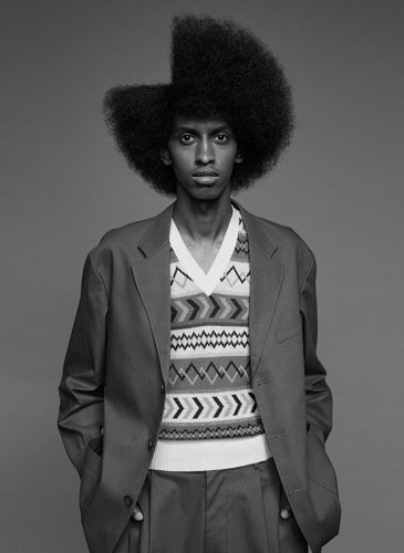A black and white photo of a male model with combed out afro hair, shaped in a 245 parting style. Taken from the 'Outside the Lines' collection by Helen Kenny