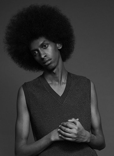A black and white photo of a male model with combed out hair in a full afro. He is shown from the waist up, wearing a dark grey sweater vest and is looking directly down the lens with his hands clasped and head tilted slightly to his right. Taken from the 'Outside the Lines' collection by Helen Kenny