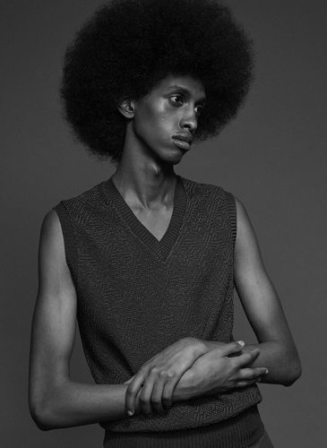 A black and white photo of a male model with combed out hair in a full afro. He is shown from the waist up, wearing a dark grey sweater vest and is looking out of the frame to his left. Taken from the 'Outside the Lines' collection by Helen Kenny