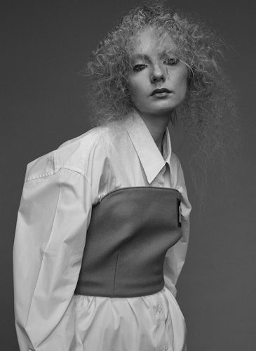 A black and photo of a female model with crimped blonde hair that is styled in a half-up bouffant. She is facing the camera and shot from the waist up, while wearing a voluminous white blouse and grey strapless top. Taken from the 'Outside the Lines' collection by Helen Kenny