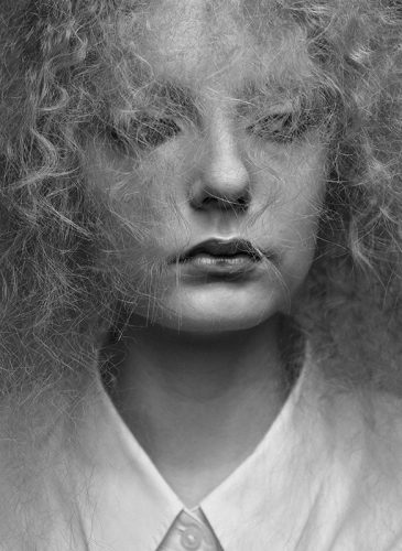 A black and photo of a female model with crimped blonde hair that is styled in a half-up bouffant. She is sat close to the camera to highlight the texture of the individual strands of hair and is facing the lens. Taken from the 'Outside the Lines' collection by Helen Kenny