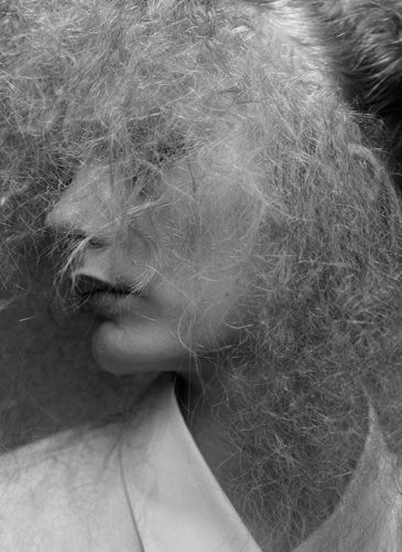 A black and photo of a female model with crimped blonde hair that is styled in a half-up bouffant. She is sat close to the camera to highlight the texture of the individual strands of hair and is looking out of the frame to her right. Taken from the 'Outside the Lines' collection by Helen Kenny