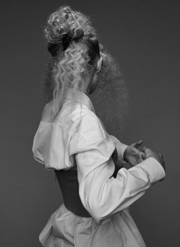 A black and photo of a female model with crimped blonde hair that is styled in a half-up bouffant. She is wearing a voluminous white blouse under a black corset and is facing away from the camera. Taken from the 'Outside the Lines' collection by Helen Kenny