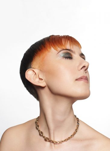 A profile, head and shoulders shot of a white female model with short hair in cropped pixie cut. The back of the style is brunette, and the front has been coloured tangerine orange, and cut in a spiked fringe. She is wearing a strapless top and a chunky gold chain. Taken from the 'Club Shapes' collection by Darcie Harvey.