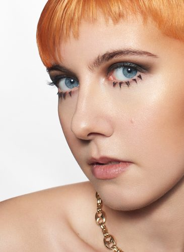 A close up shot of a white female model with short hair in cropped pixie cut. The back of the style is brunette, and the front has been coloured tangerine orange, and cut in a spiked fringe. She is wearing a chunky gold chain and has 1960s-style spiky false lashes on her lower lids. Taken from the 'Club Shapes' collection by Darcie Harvey.