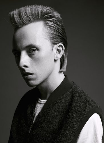 A black and white shot of a male model with a short mohawk style. The style has been cut with sharp edges and the sides are slicked back. He is wearing a grey and white basebell jacket and has been shot in profile, from the shoulders up. Taken from 'My Every Changing Moods' collection by Manifesto