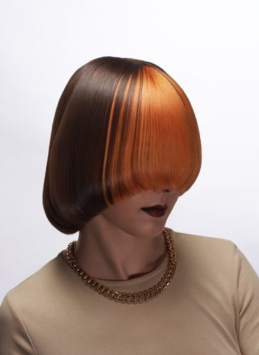 A profile, head and shoulders shot of a white female model with hair in a long pageboy bob. The back of the style is brunette, and the front has been coloured tangerine orange, and hangs over her face, covering her nose. She is wearing a beige top and a chunky gold chain. Taken from the 'Club Shapes' collection by Darcie Harvey.