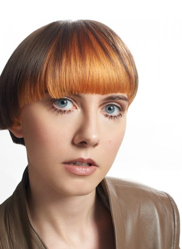 A head and shoulders shot of a white female model with short hair in cropped asymmetric cut. The back of the style is brunette, and the front has been coloured tangerine orange, and cut in a blunt fringe. She is wearing a brown leather jacket with collar. Taken from the 'Club Shapes' collection by Darcie Harvey.