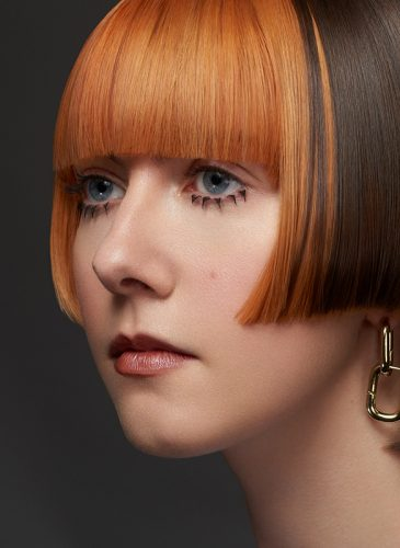 A close up shot of a white female model with short hair in staggered bob cut. The back of the style is brunette, and the front has been coloured tangerine orange, and cut in a blunt fringe. She is wearing gold drop earrings and 1960s-style spiky false lashes on her lower lids. Taken from the 'Club Shapes' collection by Darcie Harvey.