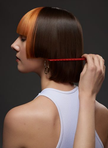 A head and shoulders profile shot of a white female model with short hair in staggered bob cut. The back of the style is brunette, and the front has been coloured tangerine orange, and cut in a blunt fringe. She is wearing a white vest top and the hand of a female hair stylist can be seen, combing through the ends with a red comb . Taken from the 'Club Shapes' collection by Darcie Harvey.