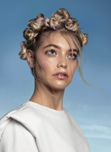 A white female model is shown in a head and shoulders shot in front of a clear blue sky. She is wearing a white, sweatshirt and has long blonde hair that has been woven with pastel pink thread and tied in several knotted buns that form a crown across her head. Taken from the collection 'Heaven' by Ivan Rodriguez.