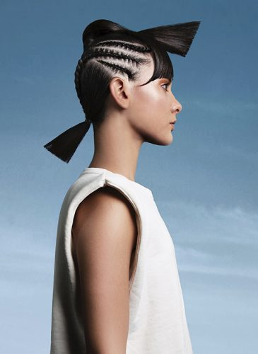 A white female model is shown in a head and shoulders shot in front of a clear blue sky. She is wearing a white, sleeveless sweatshirt and has mid-length, straight black hair that is tied back in a ponytail. Scalp braid stretch back in straight lines either side of her head, and a second ponytail braided from nape to crown lies across the top of her head, with ends forming a fringe and ponytail end across her forehead. Taken from the collection 'Heaven' by Ivan Rodriguez.