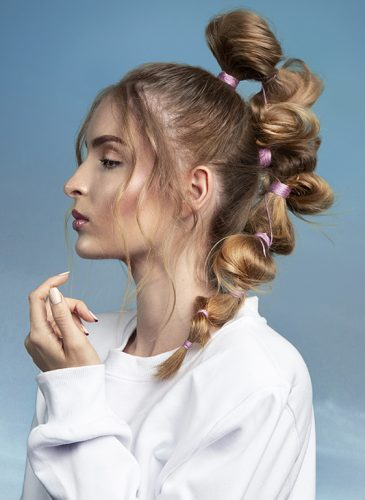 A white female model is shown in a profile-view head and shoulders shot in front of a clear blue sky. She is wearing a white sweatshirt and has long dark-blonde hair that is tied in a high ponytail. Pink thread has been wrapped around the lengths of the ponytail to create messy bubble sections, and some strands hang loose framing the model's face. Taken from the collection 'Heaven' by Ivan Rodriguez.