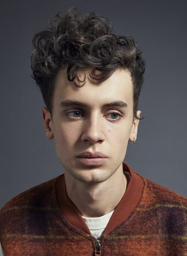 A white male model with short, dark brown curly hair. He is wearing a rust-coloured bomber jacket with a white t-shirt underneath, has a twisted gold hoop earring in his left ear and has been shot from the shoulders up. Taken from 'My Every Changing Moods' collection by Manifesto