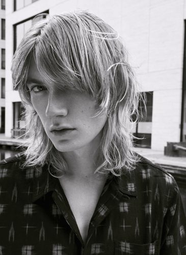 A black and white shot of a male model with dirty blonde, mid-length straight hair and a choppy curtain fringe. He is wearing a black shirt with a white square pattern and has been shot from the shoulders up. Taken from 'My Every Changing Moods' collection by Manifesto