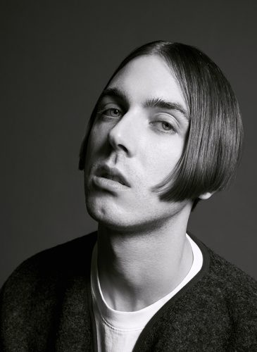 A black and white shot of a white male model with cheek-length straight, dark brown hair that has been centre-parted in a curtains style. He is wearing a black jumper with a white t-shirt underneath and has been shot from the shoulders up. Taken from 'My Every Changing Moods' collection by Manifesto