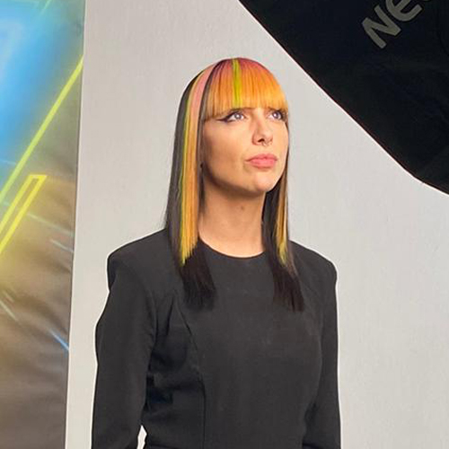 A model with mid-length, straight, dark hair and a bold orange and green coloured fringe. Coloured by Pedro Plastic at the Powered By Pulp Riot event