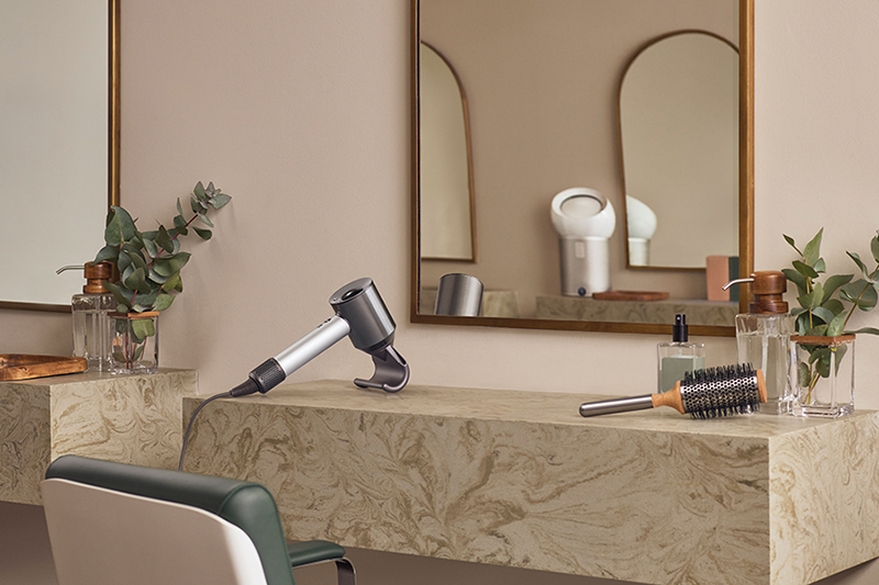A Dyson Supersonic professional hairdryer shown in front of a mirror in a salon setting