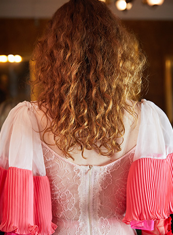 A white female model from Bora Aksu's S/S22 show at London Fashion Week is shown facing away from the camera Her long, dark blonde hair is parted in the centre and has been styled by Daniel Martin in soft natural curls.