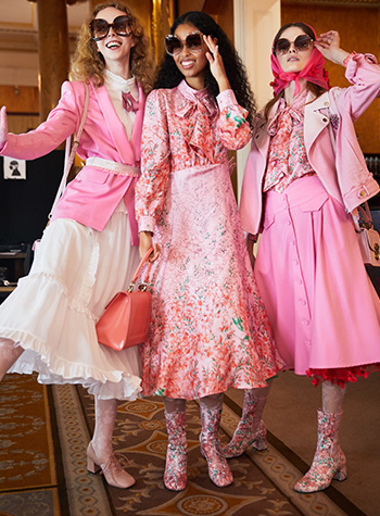 A trio of female models from Bora Aksu's S/S22 show at London Fashion Week, dressed in pink outfits with their long hair parted in the centre and styled by Daniel Martin in soft natural curls.