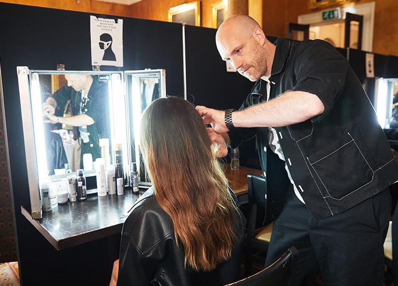 Hairdresser Daniel Martin working on a model backstage at Bora Aksu's S/S22 London Fashion Week show