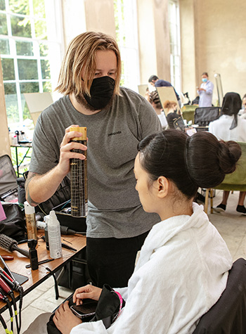 Hairdresser Shaun McIntosh works on a model backstage at Emilia Wickstead's S/S22 show at London Fashion Week.