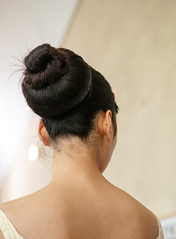 A white female model with long, dark brunette hair is shown backstage at Emilia Wickstead's S/S22 London Fashion Week show. Her hair has been swept up into an oversized, three-tiered bun by hairdresser Shaun McIntosh