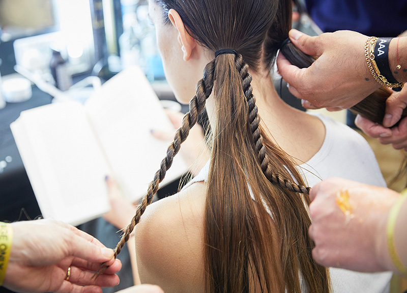 Hairdresser Ali Pirzadeh works to created twisted braid bunches on a model backstage at Rejina Pyo's S/S22 London Fashion Week show.