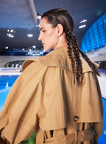 A female model with her brunette hair tied in slick bunches then formed into four twisted braids by hairdresser Ali Pirzadeh is shown backstage at Rejina Pyo's S/S22 show at London Fashion Week.