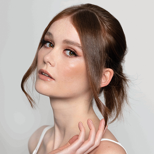 A female model with brunette hair in an ponytail, styled by Dylan Bradshaw using the Dyson Supersonic