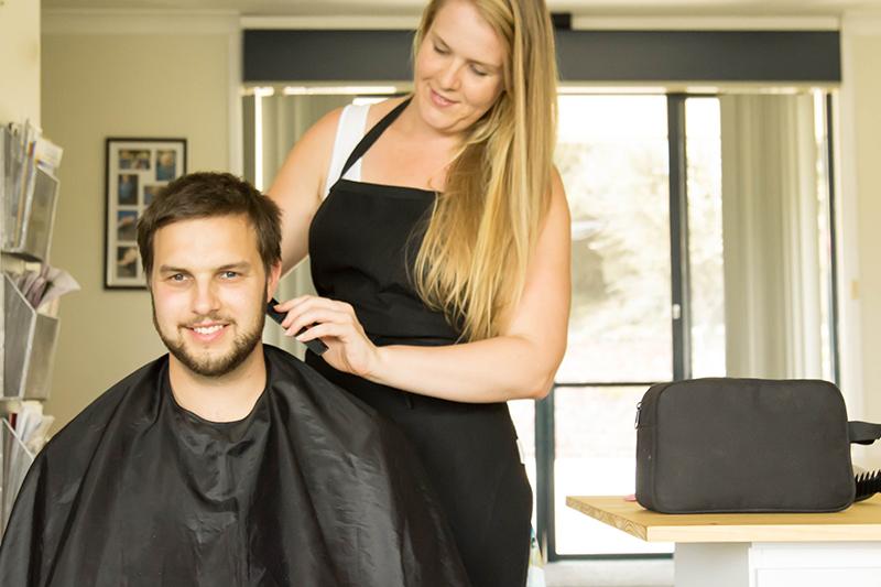 A female hairdresser cutting a male client's hair